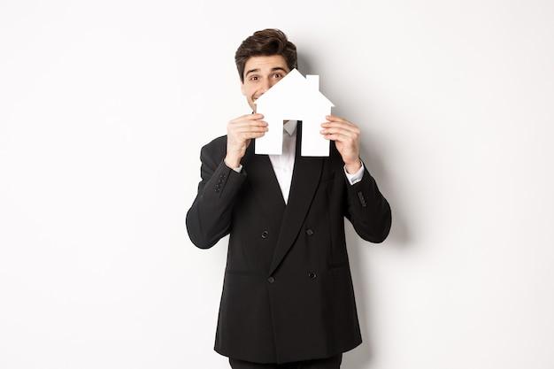 Bild eines gutaussehenden maklers im schwarzen anzug, der hausmacher zeigt und lächelt, häuser verkauft und vor weißem hintergrund steht.