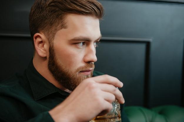 Bild eines gutaussehenden mannes, der im sessel sitzt und whisky trinkt