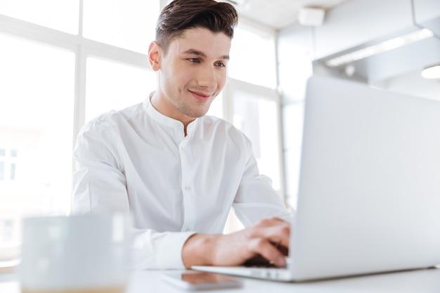 Bild eines gutaussehenden mannes, der in weißem hemd gekleidet ist und in der nähe einer tasse kaffee sitzt, während er einen laptop verwendet. coworking. computer betrachten.