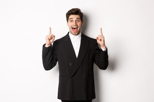 Bild eines gutaussehenden mannes im partyanzug, der ferienpromo zeigt, mit den fingern nach oben zeigt und erstaunt lächelt, auf weißem hintergrund stehend