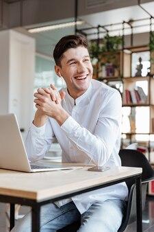 Bild eines gutaussehenden mannes im weißen hemd mit laptop-computer beim musikhören. coworking. sieh zur seite.