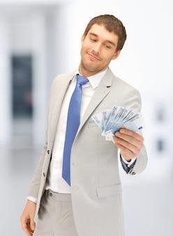 Bild eines gutaussehenden mannes mit euro-bargeld