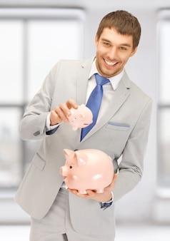 Bild eines gutaussehenden mannes mit zwei sparschweinen