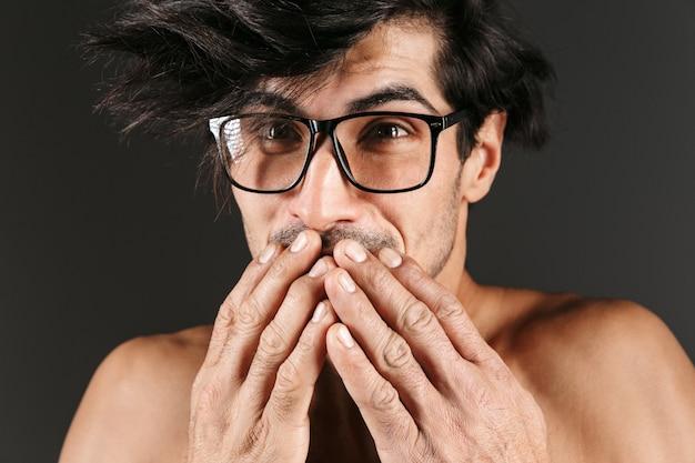 Bild eines gutaussehenden schockierten emotionalen jungen mannes, der isolierte tragende brille aufwirft.