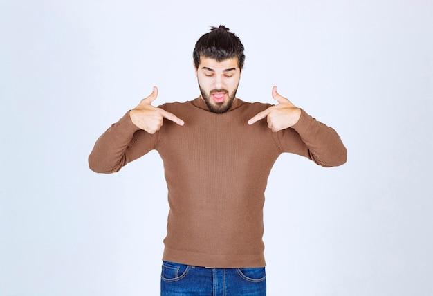 Bild eines gutaussehenden typenmodells, das mit den zeigefingern auf sich selbst zeigt. foto in hoher qualität