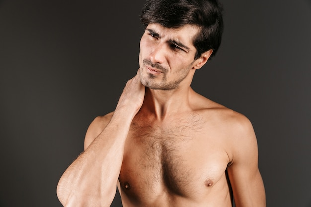 Bild eines gutaussehenden unzufriedenen jungen mannes mit nackenschmerzen, die isoliert aufwerfen.