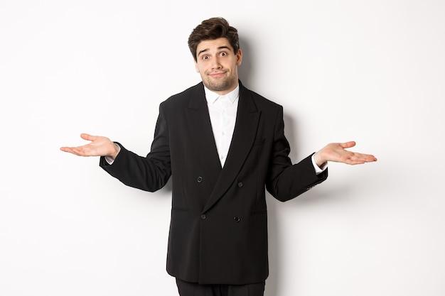 Bild eines gutaussehenden verwirrten mannes im schwarzen anzug, der mit den schultern zuckt und ahnungslos aussieht, nichts weiß und auf weißem hintergrund steht.