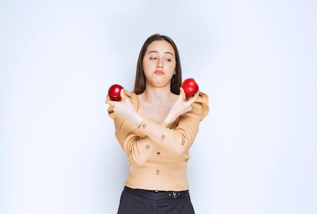 Bild eines hübschen frauenmodells, das frische rote äpfel steht und hält.