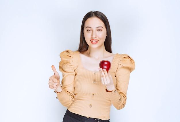 Bild eines hübschen frauenmodells, das frischen roten apfel hält und einen daumen nach oben zeigt.