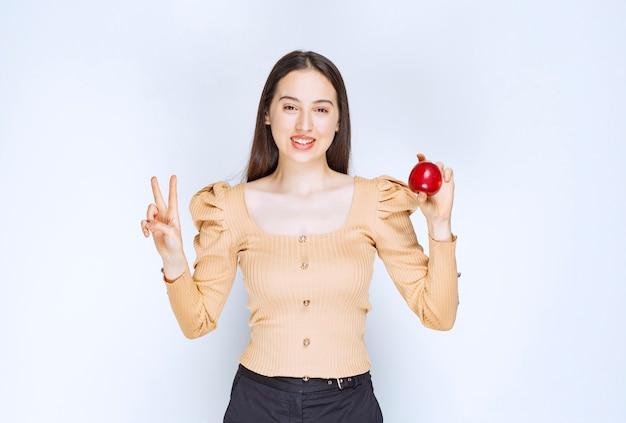 Bild eines hübschen frauenmodells, das frischen roten apfel hält und victory-zeichen zeigt.