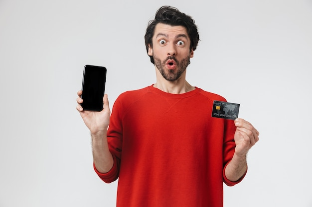 Bild eines hübschen jungen aufgeregten mannes, der über weiße wand, die kreditkarte und handy hält, aufwirft.