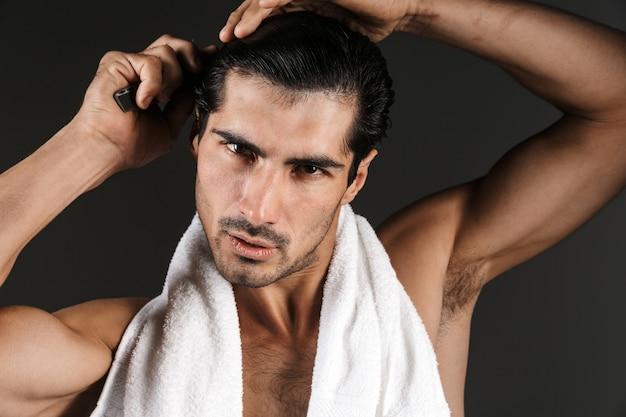 Bild eines hübschen jungen mannes, der isoliert sein haar bürstend aufwirft.