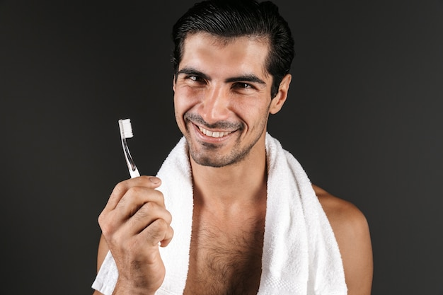 Bild eines hübschen jungen mannes, der isoliertes zähneputzen aufwirft, das seine zähne reinigt.