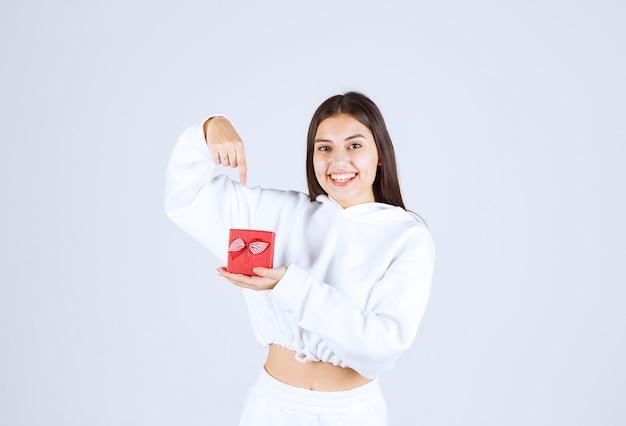 Bild eines hübschen modells des jungen mädchens, das auf eine geschenkbox zeigt.