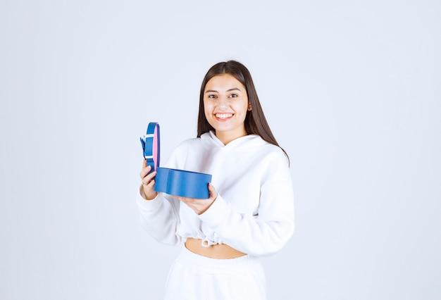 Bild eines hübschen modells des jungen mädchens, das eine herzförmige geschenkbox hält.