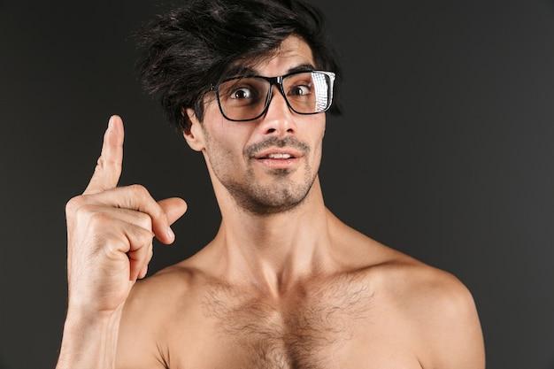 Bild eines hübschen nackten jungen mannes, der isoliertes tragen der brille zeigt zeigt.