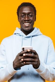 Bild eines jungen afroamerikaners im streetwear-hoodie, der lächelt und handy hält