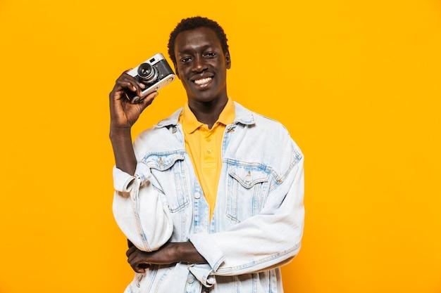 Bild eines jungen afroamerikaners in jeansjacke, der auf retro-kamera lächelt und fotografiert