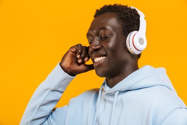 Bild eines jungen afroamerikaners mit kopfhörern, der lächelt und musik hört