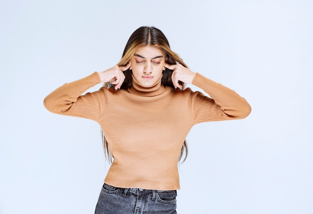 Bild eines jungen frauenmodells im braunen pullover, der die ohren mit den fingern bedeckt.