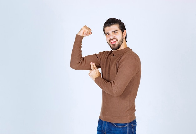 Bild eines jungen gutaussehenden mannes, der seine muskeln steht und zeigt. foto in hoher qualität