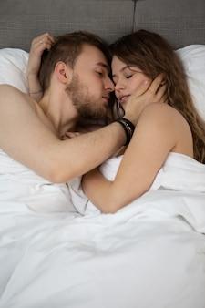 Bild eines jungen liebenden paares drinnen im haus im bett liegt umarmend und küssend.