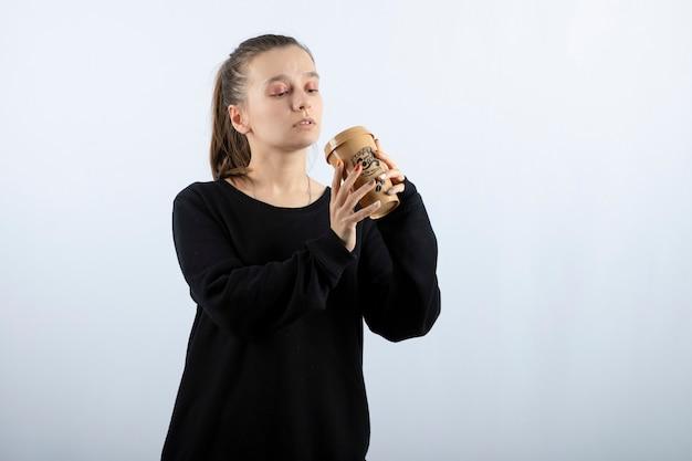 Bild eines jungen mädchenmodells, das steht und aus einer tasse kaffee trinkt