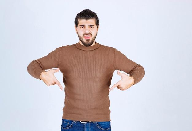 Bild eines jungen modells des gutaussehenden mannes, das unten steht und zeigt. foto in hoher qualität