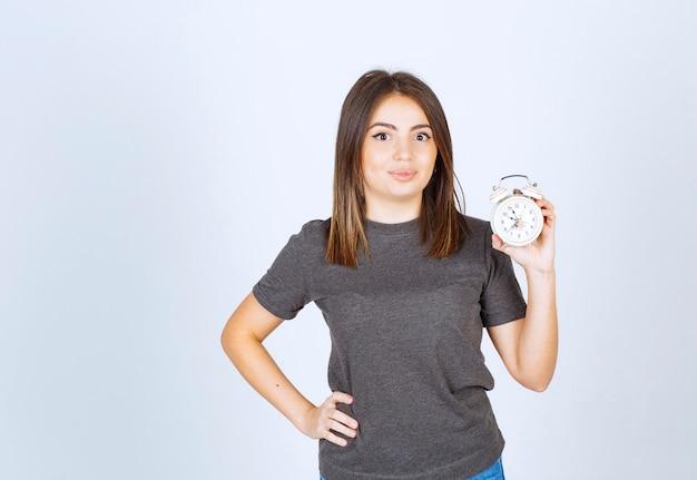 Bild eines jungen netten frauenmodells, das einen wecker zeigt.