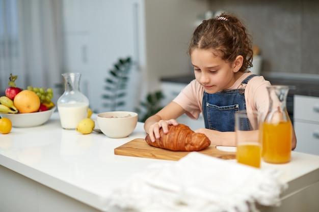 Bild eines kleinen gelockten mädchens nimmt croissant am tisch in der küche. horizontale ansicht.