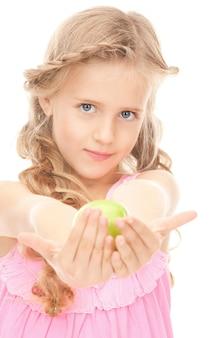 Bild eines kleinen mädchens mit grünem apfel