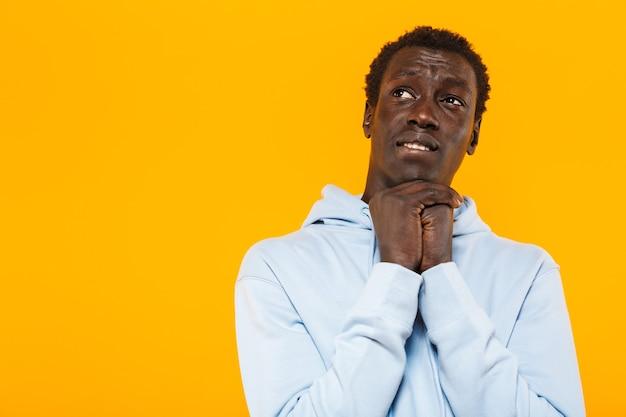 Bild eines konzentrierten afroamerikaners im streetwear-hoodie, der nach oben auf den copyspace schaut