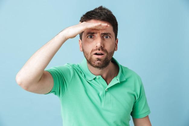 Bild eines konzentrierten jungen gutaussehenden bärtigen mannes, der isoliert über blauer wand posiert