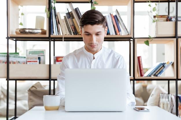 Bild eines konzentrierten mannes, gekleidet in weißes hemd mit laptop-computer. coworking. schauen sie sich den computer an.