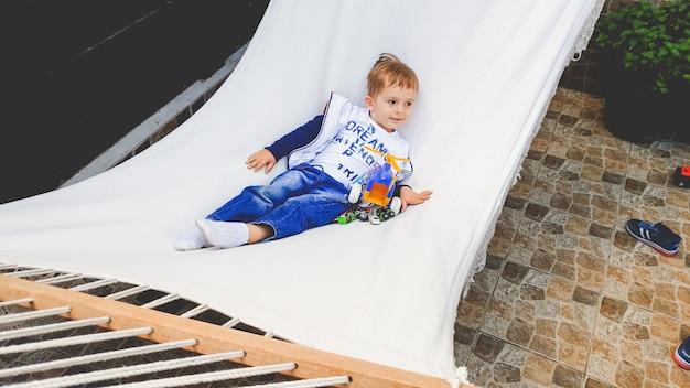 Bild eines lächelnden entzückenden kleinkindjungen, der in der hängematte im hinterhof des hauses schwingt und liegt