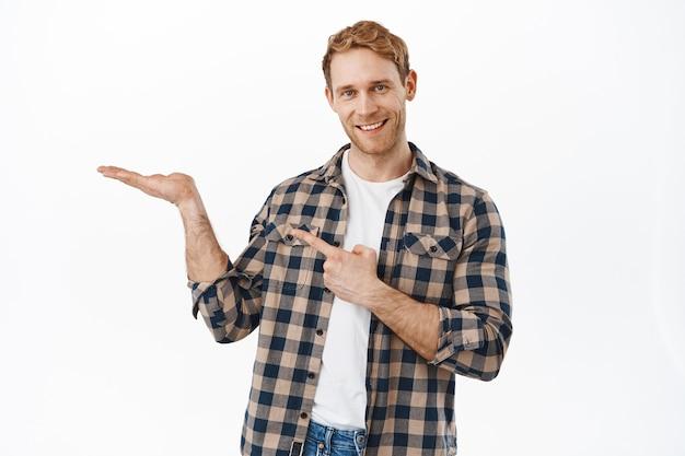 Bild eines lächelnden rothaarigen mannes, der auf seine offene hand zeigt, einen artikel anzeigt, ein produkt auf seiner handfläche empfiehlt, ein objekt zeigt und gegen eine weiße wand steht