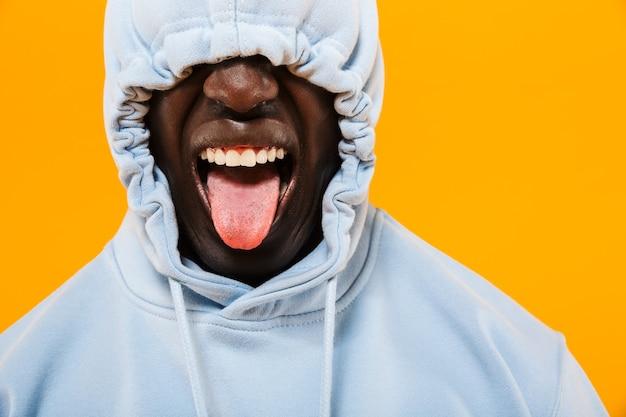 Bild eines lustigen afroamerikaners im streetwear-hoodie, der seine zunge herausstreckt