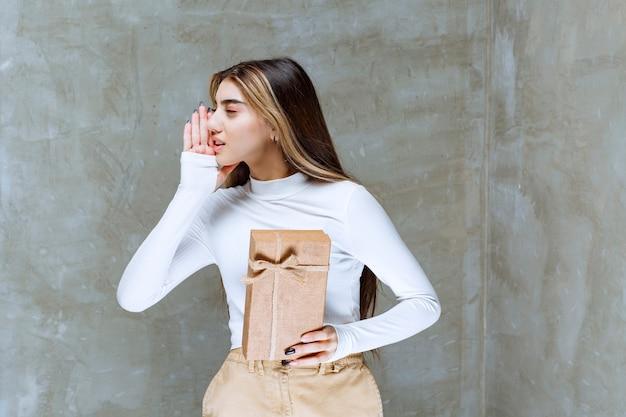 Bild eines mädchenmodells, das ein papier über stein hält