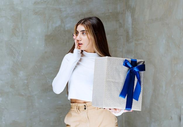 Bild eines mädchenmodells, das eine geschenkbox mit bogen lokalisiert über stein hält