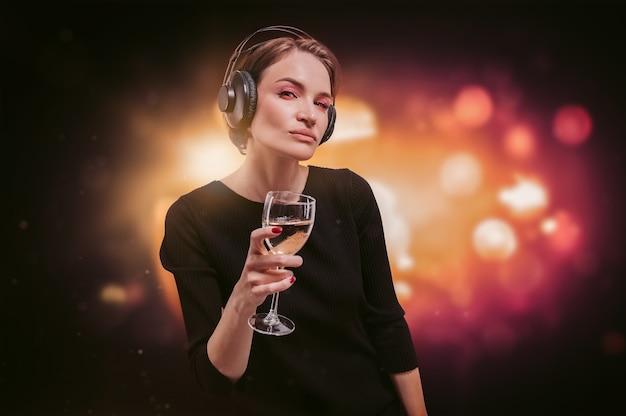 Bild eines mädchens in einem schwarzen kleid mit einem glas wein in der hand in einem nachtclub. professionelle kopfhörer. party-konzept. gemischte medien