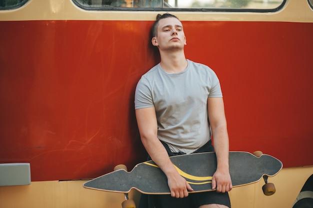 Bild eines mannes mit dem longboard, das auf straße geht