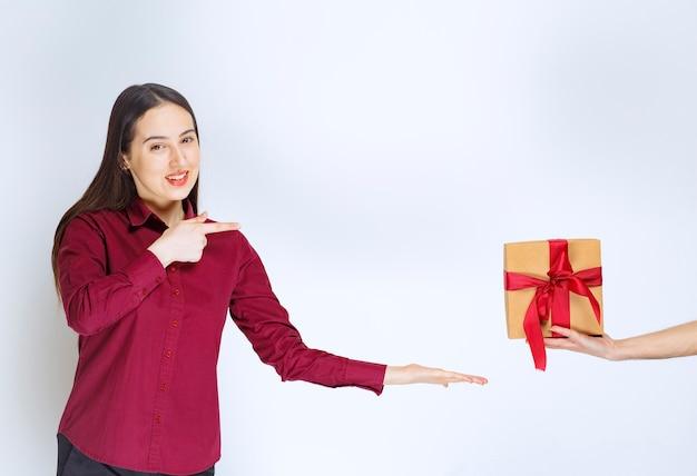 Bild eines modells der jungen frau, das auf ein geschenk mit bogen auf weißer wand zeigt.