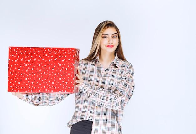 Bild eines modells der jungen frau, das eine rote geschenkbox steht und hält.