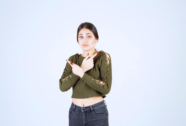 Bild eines modells der jungen frau, das mit dem zeigefinger beiseite steht und zeigt.