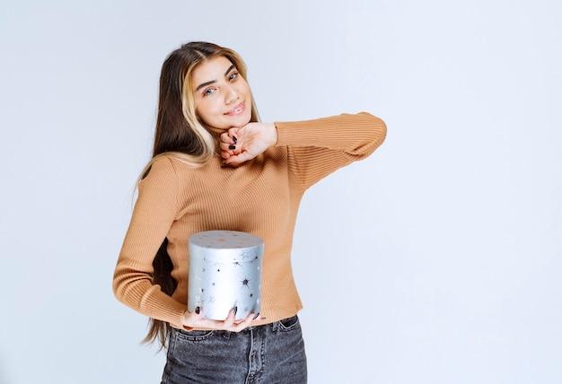 Bild eines modells der jungen frau in der braunen strickjacke, die mit einer geschenkbox steht und aufwirft.
