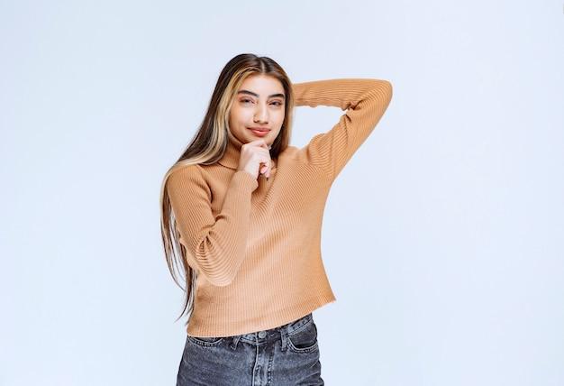Bild eines modells der jungen frau in der braunen strickjacke, die steht und aufwirft.