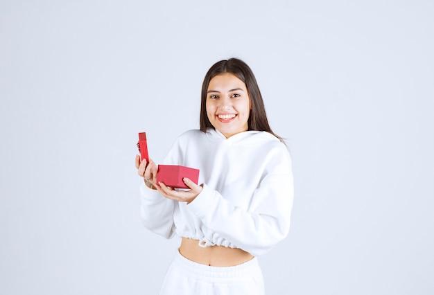 Bild eines modells des hübschen jungen mädchens, das eine geschenkbox hält. h