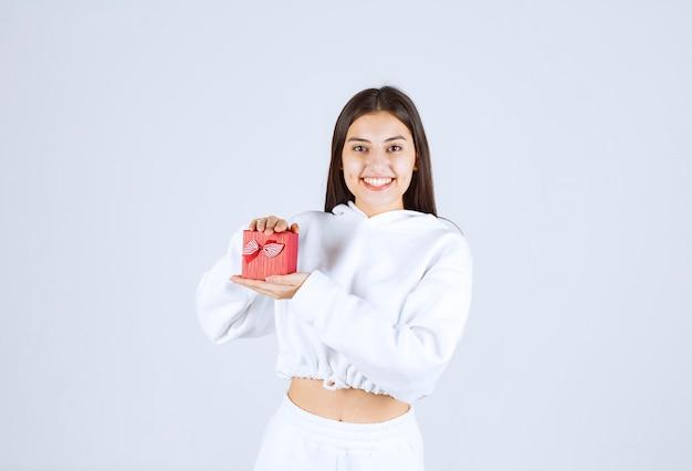 Bild eines modells des hübschen jungen mädchens, das eine geschenkbox hält.