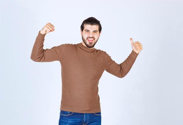 Bild eines modells des jungen mannes, das mit einem daumen rückwärts steht und zeigt. foto in hoher qualität