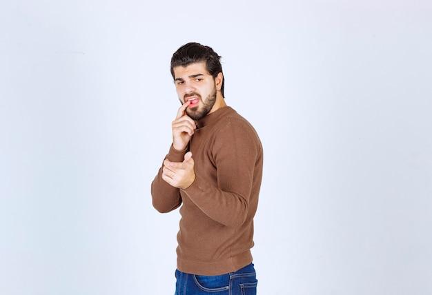 Bild eines modells des jungen mannes, das seinen finger steht und beißt. foto in hoher qualität